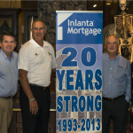 Inlanta Mortgage's Senior Management Team standing by banner